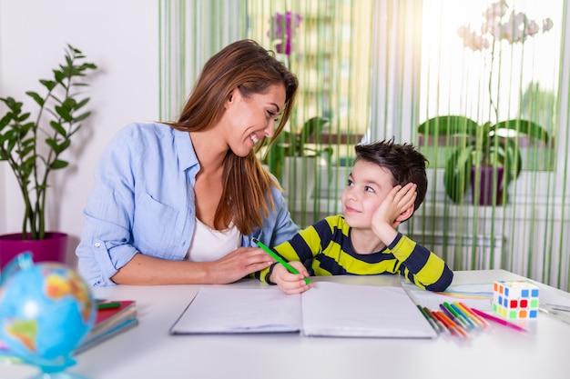 Moeder die met huiswerk helpt aan haar zoon binnen. familie, kinderen en gelukkige mensen concept.