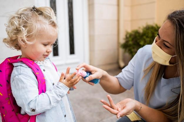 Moeder die met medisch masker de handen van het kind met ontsmettingsmiddel sproeien