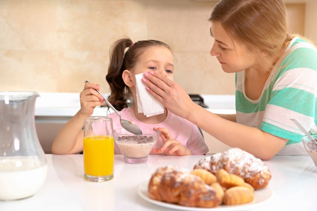 Moeder die ontbijt met haar dochter heeft bij een lijst in keuken, gelukkig alleenstaand moederconcept