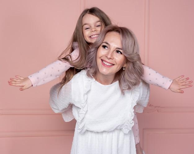 Moeder die op de rug rit geeft aan dochter