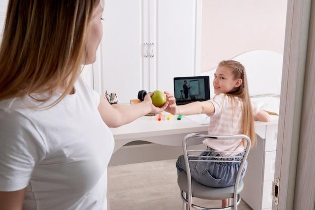 Moeder die op haar dochter let die thuiswerk op laptop doet die thuis ruimte ingaat en groene appel geeft
