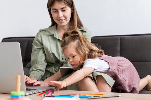 Moeder die op laptop met kind werkt