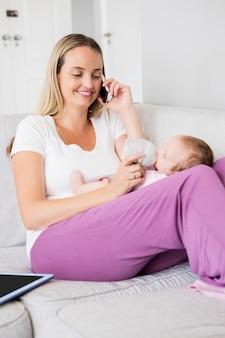 Moeder die op mobiele telefoon spreekt terwijl het voeden van haar baby met melkfles
