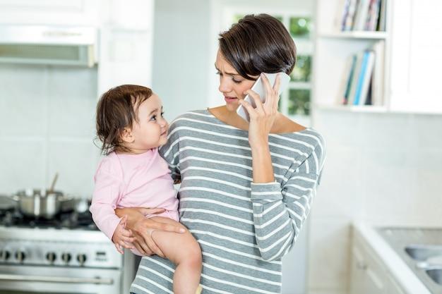 Moeder die op smartphone met dochter in keuken spreekt