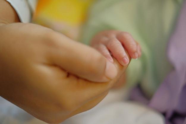 Moeder die pasgeboren babyhand vasthoudt