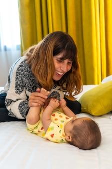 Moeder die plezier heeft met haar baby op het bed in haar slaapkamer, jonge kaukasische eerste keer met haar vier maanden oude baby, verticale foto