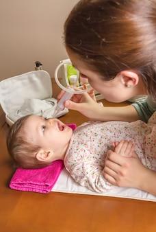 Moeder die slijmverval van schattige baby schoonmaakt met een neusaspirator