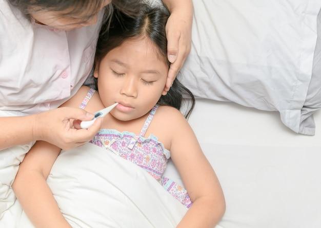 Moeder die temperatuur van ziek jong geitje meet.