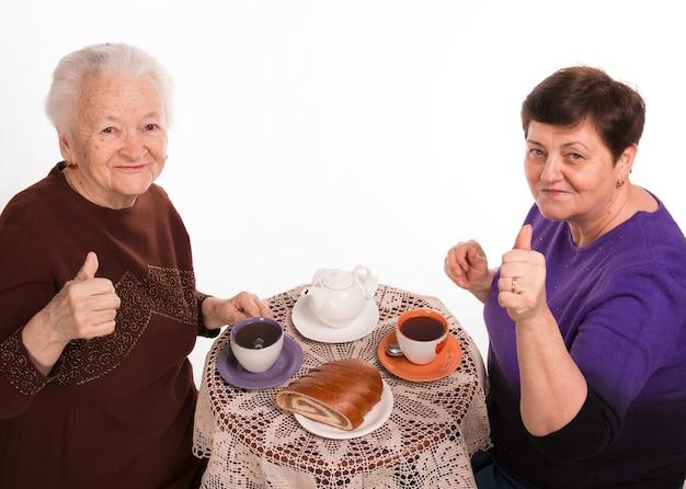 Moeder die thee met haar dochter op een wit heeft