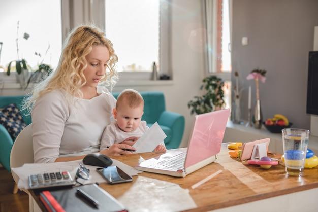 Moeder die thuis bureau met haar baby werkt