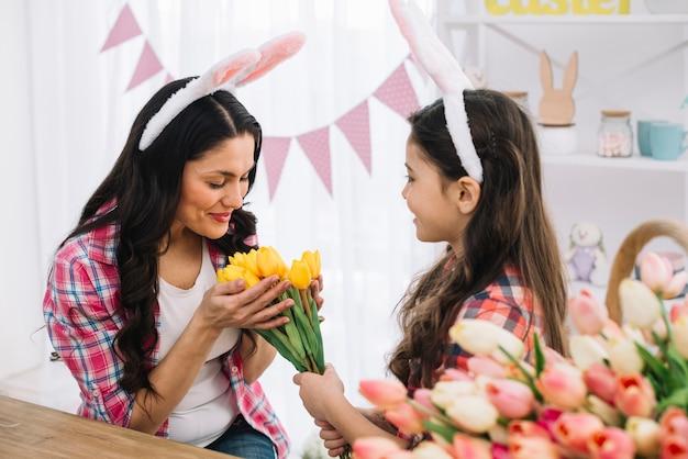 Moeder die van het gele die tulpenboeket houdt door haar dochter op pasen-dag wordt gegeven