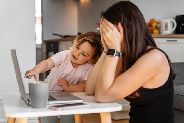 Moeder die van huis met babypeuter werkt. huilend kind en gestresste vrouw. blijf thuis