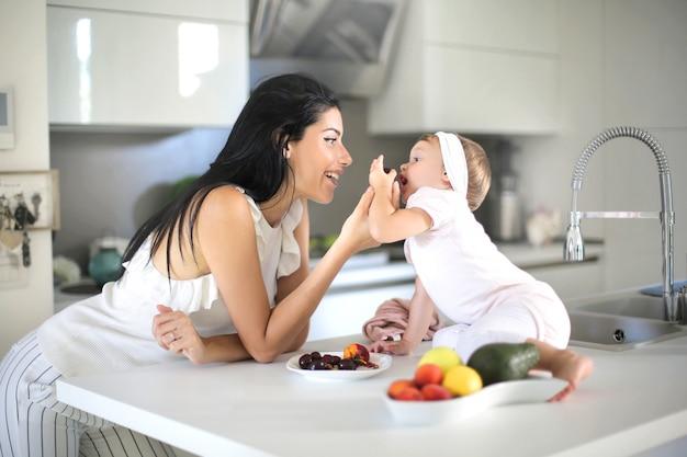Moeder die voedsel geeft aan haar baby in de keuken