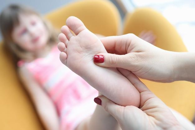 Moeder die voetmassage geeft aan klein meisje thuis close-up