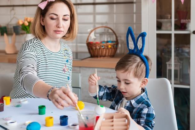 Moeder die weinig jongen onderwijst hoe te om eieren voor pasen te schilderen