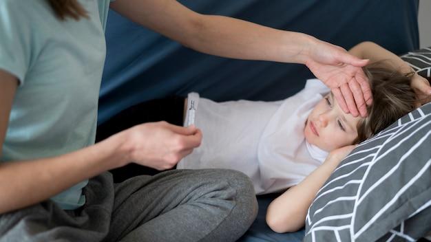 Moeder die zijn zoon controleert op koorts