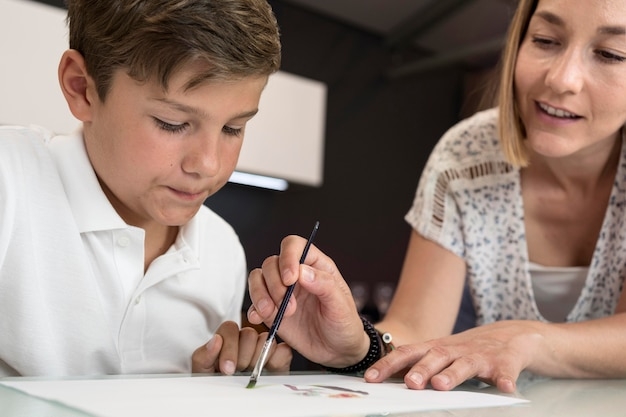 Moeder die zoon helpt om het schilderen te beëindigen