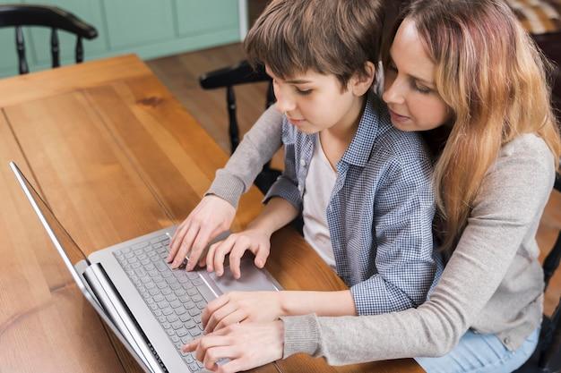 Moeder die zoon onderwijst hoe een laptop te gebruiken