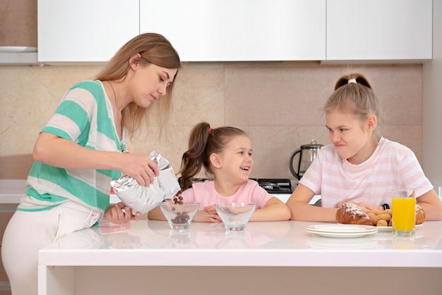 Moeder dienend ontbijt aan haar twee dochters bij een lijst in keuken, gelukkig alleenstaand moederconcept