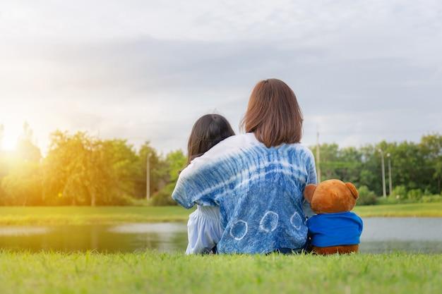 Moeder, dochter en teddyberen zitten genieten van de natuur op een mooie dag