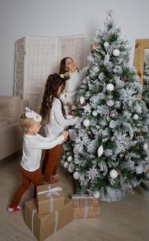 Moeder, dochter en zoon die kerstboom versieren
