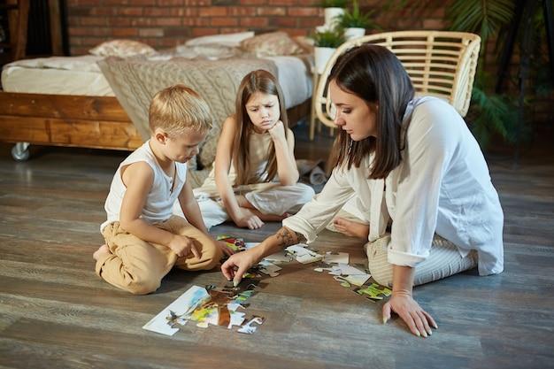 Moeder dochter en zoon legden de puzzel in elkaar op de vloer. familie-entertainment. vrouw meisje en jongen spelen samen
