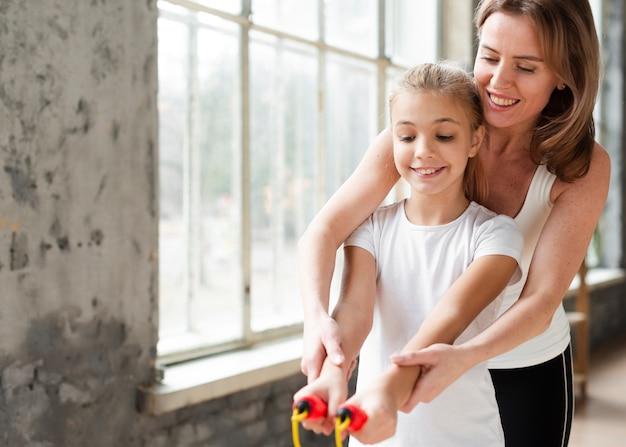 Moeder dochter onderwijzen hoe springtouw te gebruiken