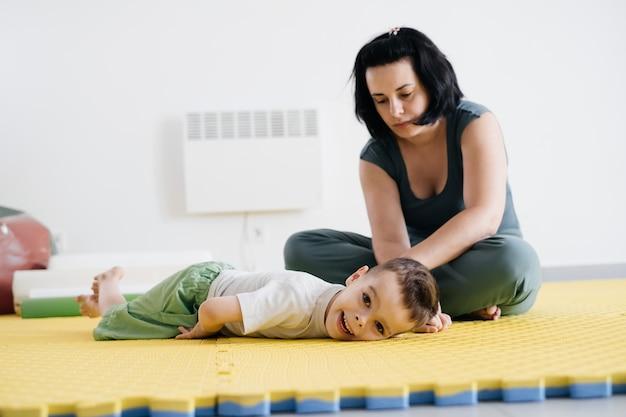 Moeder doet fysieke oefeningen en speelt met gehandicapte jongen