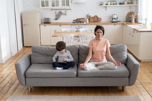 Moeder doet yoga oefening, zittend op de bank thuis, kind met behulp van gadget, een spel spelen op tablet.