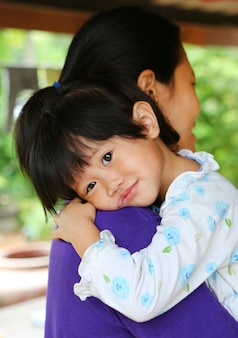 Moeder draagt aziatische kind meisje in haar armen.