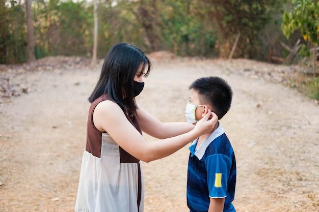 Moeder draagt een masker om haar zoon te beschermen tegen het covid-19-virus.