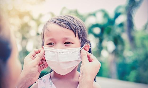 Moeder draagt een stoffen masker voor een klein meisje dat zichzelf beschermt tegen coronavirus of luchtvervuiling