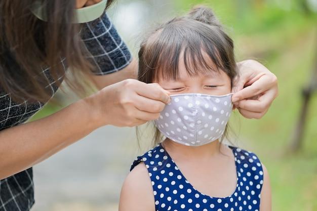Moeder draagt een stoffen masker voor klein meisje, beschermt tegen coronavirus wanneer het kind het huis verlaat