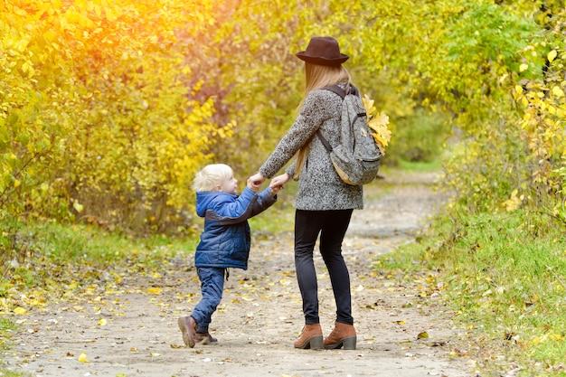 Moeder draait zijn zoon in de herfst in het bos.