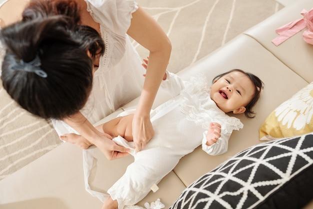 Moeder dressing babymeisje