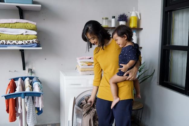 Moeder een huisvrouw met een baby die zich bezighoudt met wasgoed met een wasmachine