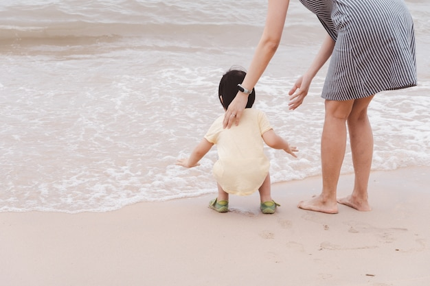 Moeder en aziatische jongen spelen op het strand.