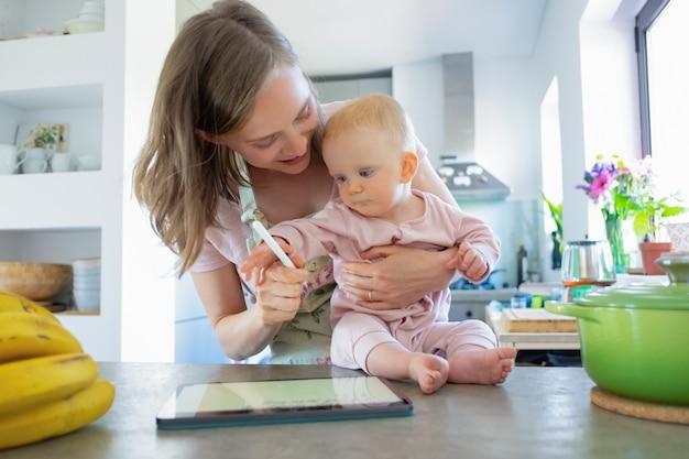 Moeder en baby dochter samen koken thuis, kijken naar recepten op tablet. kinderopvang of koken thuis concept