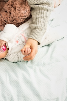 Moeder en baby hand in hand op bed