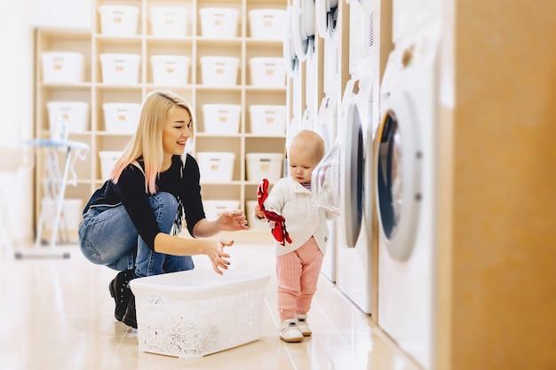 Moeder en baby in de was nemen dingen en spelen