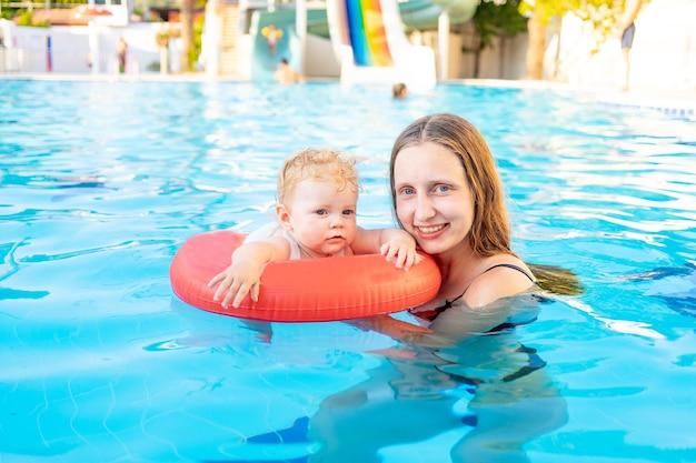Moeder en baby in een opblaasbare cirkel in het zwembad met glijbanen in de zomer veel plezier met zwemmen, ontspannen en tijd doorbrengen, moeder leert het kind zwemmen