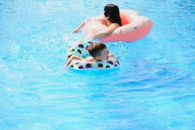 Moeder en baby in het buitenzwembad van tropische resort. moeder en kind spelen in het water.