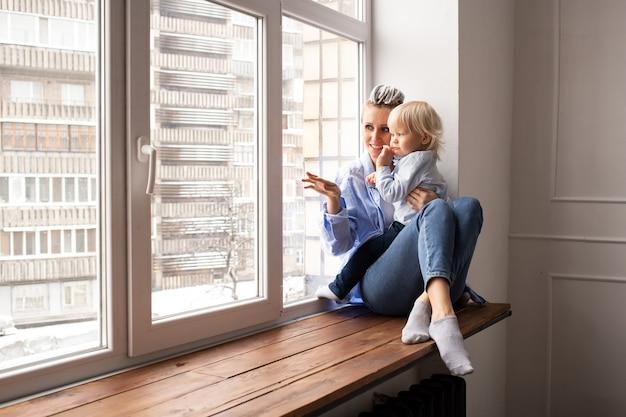 Moeder en baby jongenskind kijken door raam in quarantaine