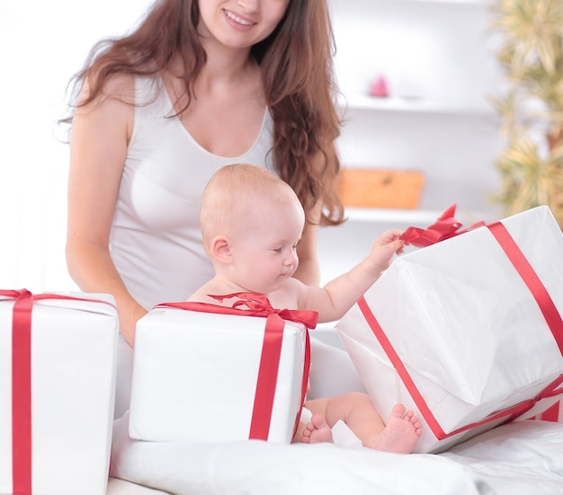 Moeder en baby kijken naar geschenkdozen. vakantieconcept