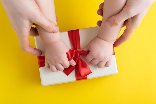 Moeder en baby maken de strik van het geschenk los. bovenaanzicht.