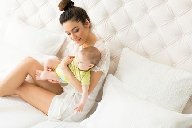 Moeder en baby meisje op het bed