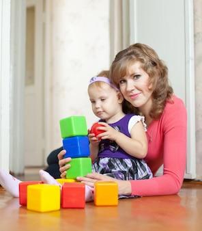 Moeder en baby meisje speelt met blokken in huis