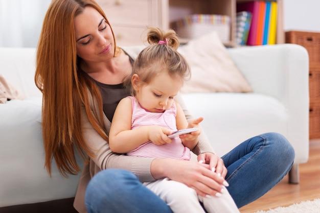 Moeder en baby met mobiele telefoon thuis