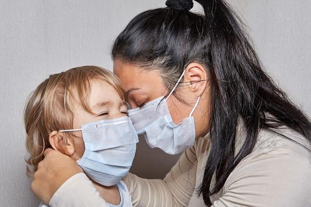 Moeder en baby, mooie dochter, krijgen allebei medische maskers op hun gezicht als bescherming tegen infecties tijdens chronische ziekten.