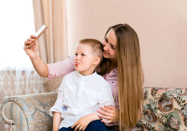 Moeder en baby nemen een selfie in een gezellige woonkamer. moeder en zoon trekken grappige gezichten en nemen foto's van zichzelf op camera